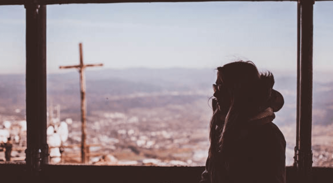 Girl looking out window at a cross