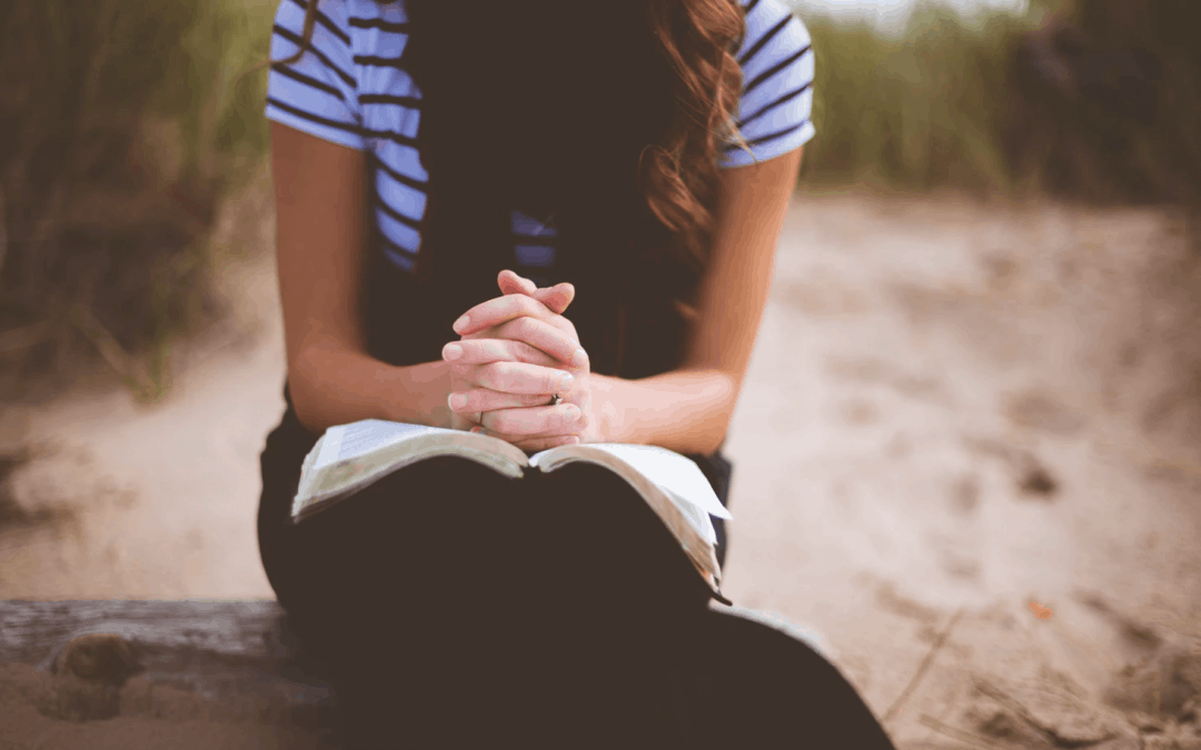 Woman in blue shirt with her head down and fingers laced in prayer over an open Bible