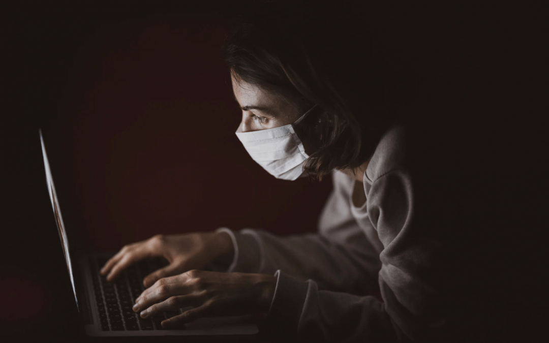Woman with mask at a laptop
